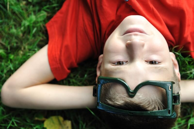 Cute positive boy with glasses laying on green grass ground and looking up at camera and thinking